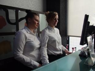 Dwie Martyny obserwujące obsługę gości w recepcji hotelowej